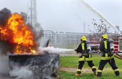 Zwei Feuerwehrmänner, die ein großes Flammenfeuer kämpfen Stockfoto