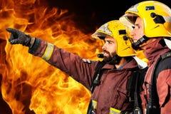 Zwei Feuerwehrmänner, die Feuer analysieren Stockbild