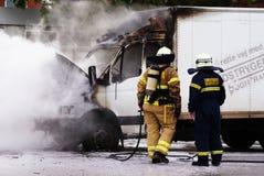 Zwei Feuerwehrmänner mit brennendem LKW stockfoto