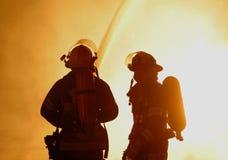 Zwei Feuerwehrmänner an rasendem Feuer Stockfoto