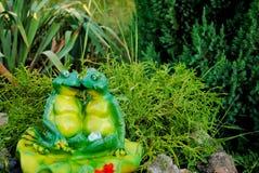 Zwei Figürchen des grünen Frosches, die in einer Umarmung gegen einen Hintergrund von grünen Büschen sitzen Lizenzfreie Stockbilder