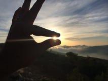 Zwei Finger, welche die Sonne halten Stockfotos