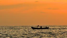 Zwei Fischer nehmen ein kleines Fischerboot zum Meer bei Sonnenuntergang Stockfoto