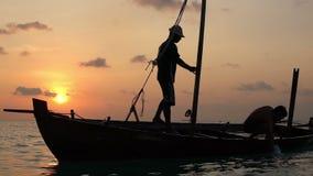 Zwei Fischer waschen altes Boot bei Sonnenuntergang im Indischen Ozean Langsame Bewegung stock video footage