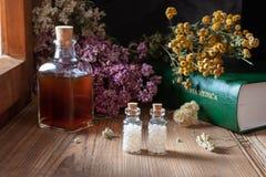Zwei Flaschen homöopathische Pillen mit getrockneten Kräutern und materia medica stockfoto