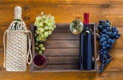 Zwei Flaschen mit Gläsern Wein und Trauben auf einem hölzernen Hintergrund stockfotografie