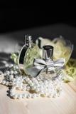 Zwei Flaschen weibliches Parfüm und Perlen 2 lizenzfreie stockbilder