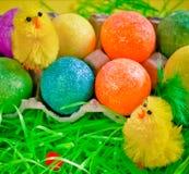 Zwei flaumige Hühnerspielwaren nahe bunten hellen Eiern lizenzfreie stockbilder