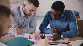 Zwei fokussierten junge männliche Manager arbeiten zusammen mit Architekturskizze durch die Tabelle im modernen hellen multiethni stock video