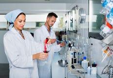 Zwei Forscher im weißen Mantel Weinsäure im Labor überprüfend stockfoto