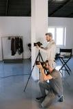 Zwei Fotografen, die Schüsse im Studio nehmen stockbild