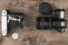 Zwei Fotokameras auf altem Holztisch, Draufsicht Vergleich von verschiedenen Generationen des Fotografierens der Ausrüstung Lizenzfreies Stockbild