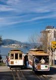 Zwei Francisco-Standseilbahnen mit Alcatraz im Hintergrund Lizenzfreies Stockbild