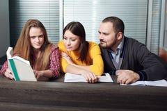Zwei Frau und Mann, die ein Buch Geschäft lesen Lizenzfreies Stockbild