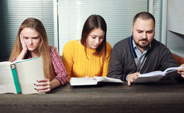 Zwei Frau und Mann, die ein Buch Geschäft lesen Lizenzfreie Stockbilder