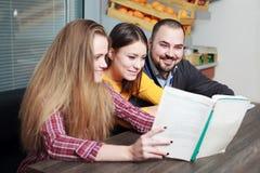 Zwei Frau und Mann, die ein Buch Geschäft lesen Lizenzfreie Stockfotos