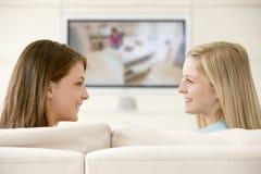 Zwei Frauen in überwachendem Fernsehen des Wohnzimmers Stockfotografie