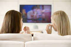 Zwei Frauen in überwachendem Fernsehen des Wohnzimmers lizenzfreies stockfoto