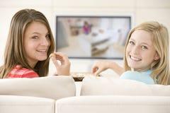 Zwei Frauen in überwachendem Fernsehen des Wohnzimmers Lizenzfreies Stockbild