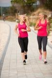 Zwei Frauen athlets, die auf dem Strand - Sommer w des frühen Morgens laufen Stockbild
