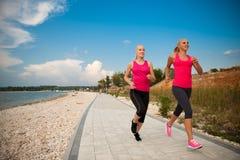 Zwei Frauen athlets, die auf dem Strand - Sommer w des frühen Morgens laufen Stockfotografie