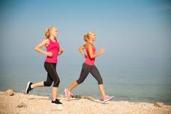 Zwei Frauen athlets, die auf dem Strand - Sommer w des frühen Morgens laufen Stockbilder