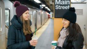 Zwei Frauen auf einer Plattform eines New- Yorku-bahnstations-Wartung ihren Zug lizenzfreies stockbild