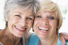 Zwei Frauen beim Wohnzimmerlächeln Stockbild