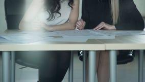Zwei Frauen besprechen etwas, das auf Dokumenten an Bord Innen niedrig ist stock video