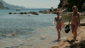 Zwei Frauen in den Bikinis schlendernd auf den allgemeinen Strand nahe den Bergen stock video