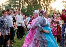 Zwei Frauen in den bunten russischen Kostümen, tanzend während der Zeit des jährlichen internationalen Festivals Lizenzfreies Stockbild