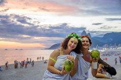 Zwei Frauen in den Kostümen von griechischen Göttinnen auf dem Hintergrund des schönen Sonnenuntergangs bei Ipanema setzen, Carna lizenzfreie stockbilder