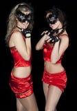 Zwei Frauen in den roten Klagen und in der Schablonenkatze Stockfotos
