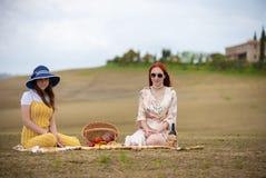 Zwei Frauen in der Sommerkleidung, die auf der Decke sitzt und ein Picknick hat stockfotografie
