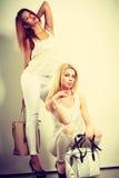 Zwei Frauen in der weißen Kleidung mit Taschenhandtaschen Stockbild