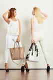 Zwei Frauen in der weißen Kleidung mit Taschenhandtaschen Lizenzfreies Stockbild