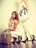 Zwei Frauen in der weißen Kleidung mit Taschenhandtaschen Lizenzfreie Stockfotos