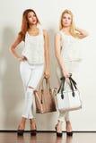 Zwei Frauen in der weißen Kleidung mit Taschenhandtaschen Stockfotografie