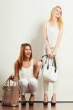 Zwei Frauen in der weißen Kleidung mit Taschenhandtaschen Stockbilder