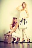 Zwei Frauen in der weißen Kleidung mit Taschenhandtaschen Lizenzfreie Stockbilder