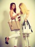Zwei Frauen in der weißen Kleidung mit Taschenhandtaschen Stockfotos