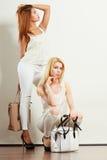 Zwei Frauen in der weißen Kleidung mit Taschenhandtaschen Stockfoto