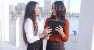 Zwei Frauen, die über einen Tablet-Computer lachen Stockbild