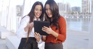 Zwei Frauen, die über einen Tablet-Computer lachen Stockfotografie