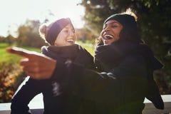 Zwei Frauen, die über etwas bei der Stellung im Park lachen stockfoto