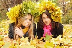 Zwei Frauen, die auf Blättern liegen stockfotografie