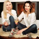 Zwei Frauen, die auf dem Pelz sitzen, legen nahe Kamin mit Teppich aus Stockfotografie