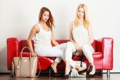 Zwei Frauen, die auf dem Sofa darstellt Taschen sitzen lizenzfreie stockfotos