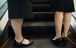 Zwei Frauen, die auf der Rolltreppe stehen Lizenzfreie Stockfotografie