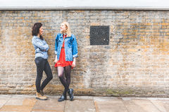 Zwei Frauen, die auf einer Wand sich lehnen und in London sprechen Lizenzfreie Stockbilder